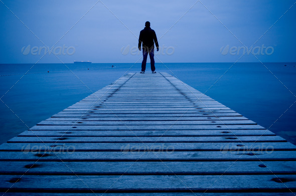 Man standing on a wooden pier - Stock Photo - Images