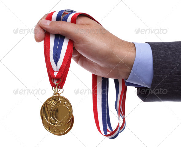 Businessman holding gold medal - Stock Photo - Images