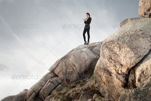 Businesswoman on a Rock - Stock Photo - Images