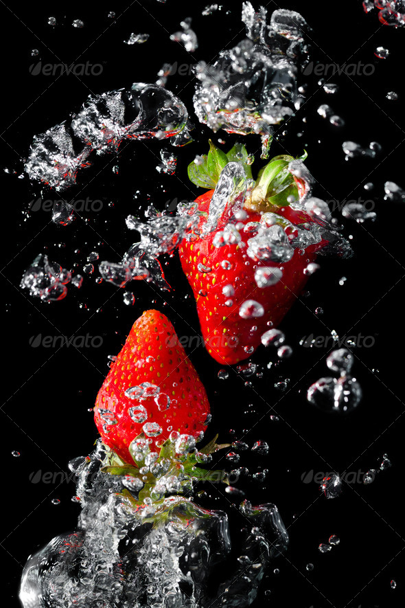 Two strawberries in the water with air bubbles - Stock Photo - Images