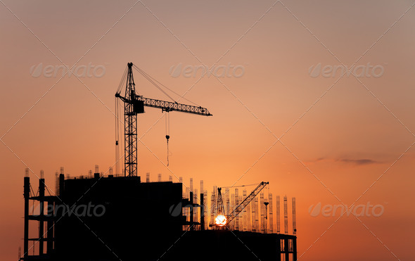Construction cranes and concrete structure at sunset - Stock Photo - Images