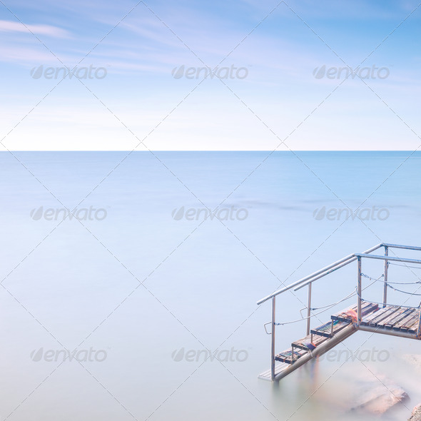 Wooden ladder pier to sea water. Long exposure. - Stock Photo - Images