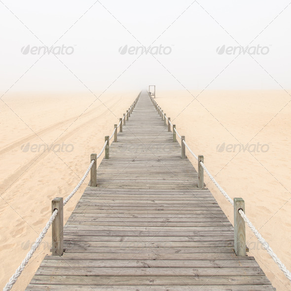 Wooden footbridge on a foggy sand beach background. Portugal. - Stock Photo - Images