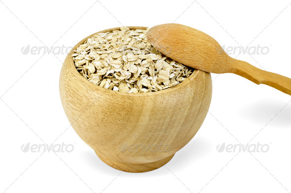 Oat flakes in a wooden bowl with a spoon - Stock Photo - Images