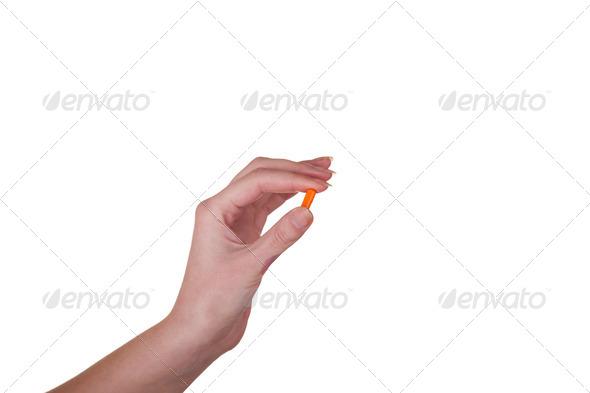 Hand holding an orange capsule isolated on white background - Stock Photo - Images