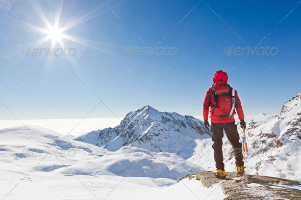 Climber looking at a snowy mountain landscape in a sunny winter day.. Western Alps, Biella, Italy. - Stock Photo - Images