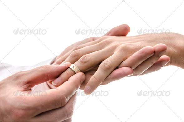Groom putting a wedding ring on the finger of the bride - Stock Photo - Images