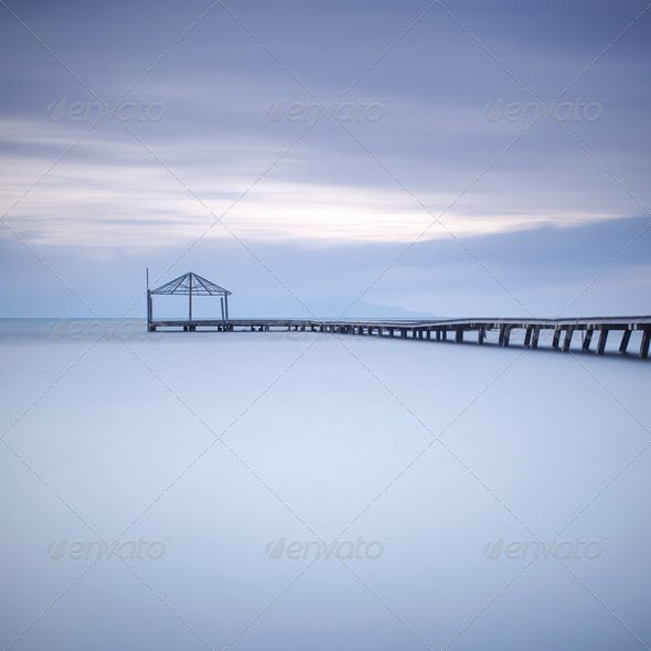 Wooden pier or jetty silhouette and blue ocean on sunset - Stock Photo - Images