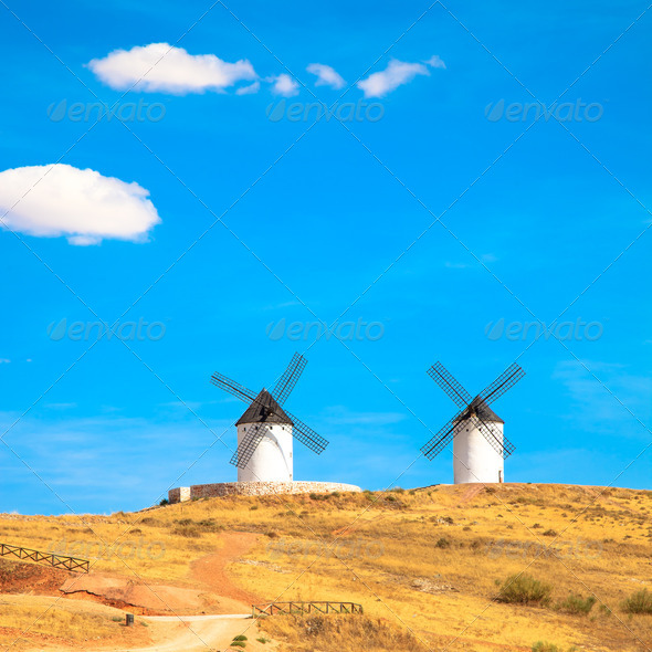 Windmills, rural green fields and blue sky. Consuegra, Spain - Stock Photo - Images