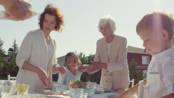 Happy Family Preparing Table for Holiday Dinner Outdoors