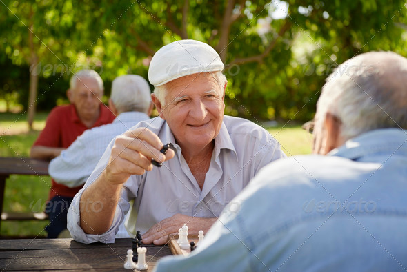 Active retired seniors, two old men playing chess at park - Stock Photo - Images