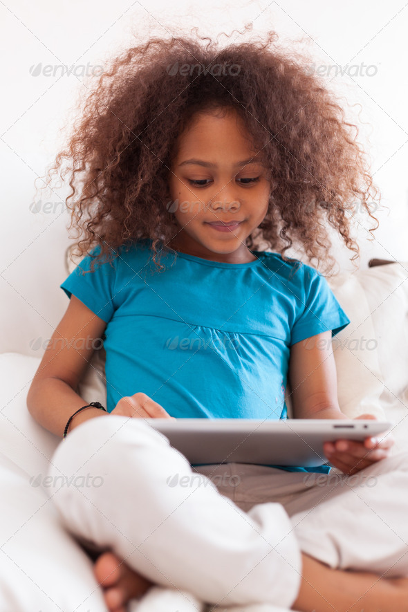 Little african asian girl using a tablet pc - Stock Photo - Images