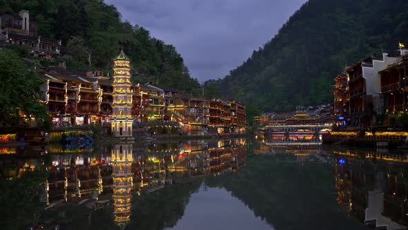 Traditional Chinese Tower and Houses on Both Banks of the River with Night Illumination During Dusk