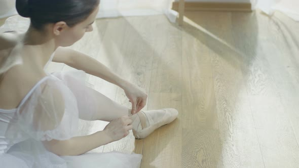 Young Beautiful Ballet Dancer Sitting On The Wooden Floor By