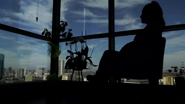 Silhouette of a Young Woman Looking Out The Window