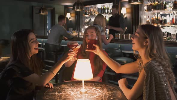 Three Happy Women Sitting at the Small Table in Bar