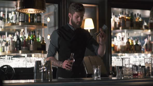 Hipster Bartender Mixologist Combining Ingredients and Making a Whiskey Cocktail in Beautiful Modern