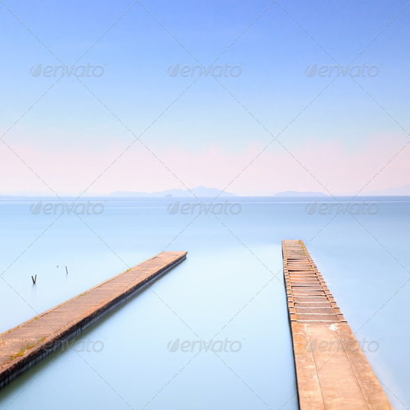 Two concrete pier or jetty on a blue sea. Hills on background - Stock Photo - Images