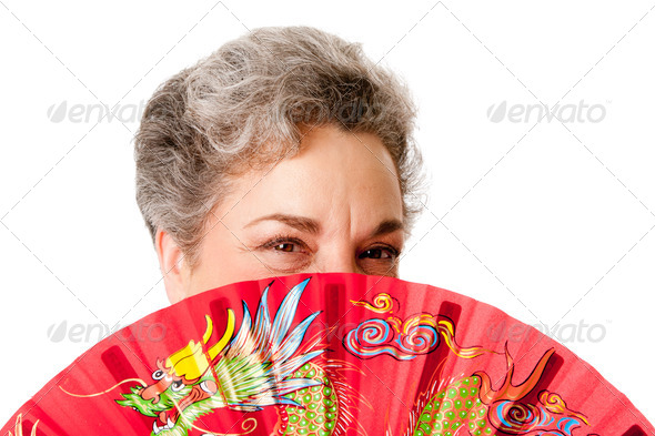 Senior woman with red dragon fan - Stock Photo - Images
