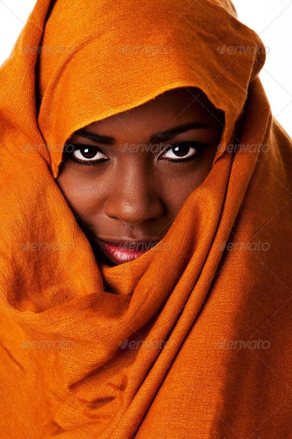 Mysterious female face in ocher head wrap - Stock Photo - Images