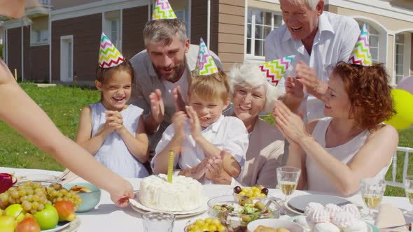 Little Boy Clapping Hands and Enjoying Birthday Cake on Family Party
