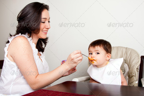 Infant eats messy - Stock Photo - Images
