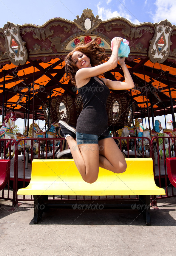 Fun girl jumping at Carousel - Stock Photo - Images