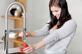Woman rinsing peppers in a sink - PhotoDune Item for Sale