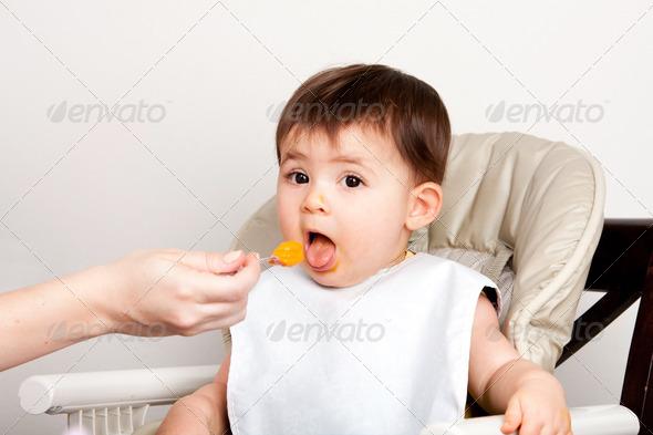 Happy baby spoon feeding - Stock Photo - Images