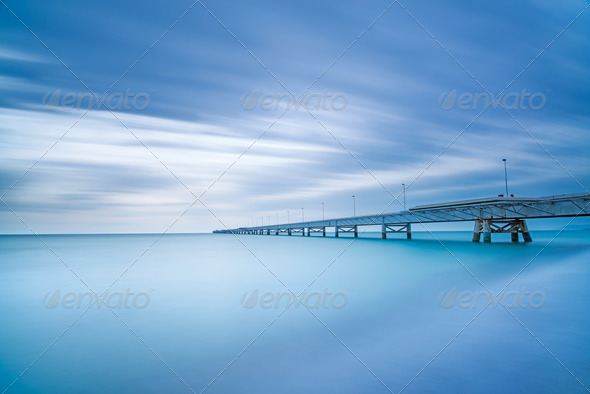Industrial pier on the sea. Side view. Long exposure photography. - Stock Photo - Images