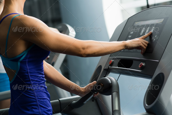 woman adjusts the treadmill - Stock Photo - Images