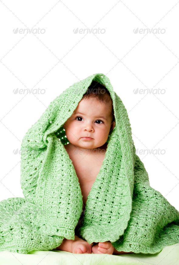 Cute baby sitting between green blanket. - Stock Photo - Images