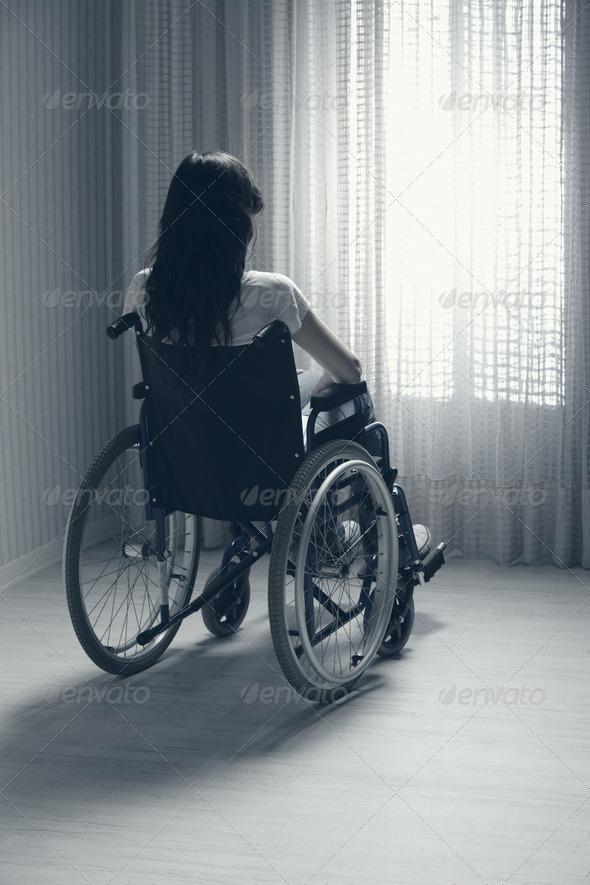 Sad woman sitting on wheelchair - Stock Photo - Images