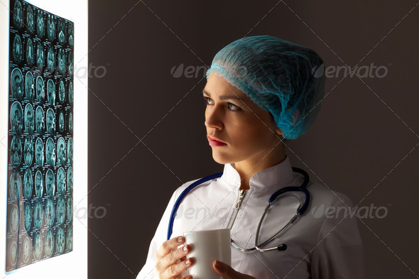Woman doctor examining x-ray - Stock Photo - Images