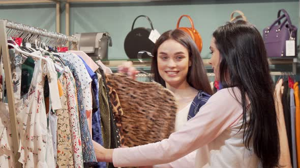 b485bb666cfff Two Lovely Young Women Shopping Together at Clothing Store (Stock Footage)