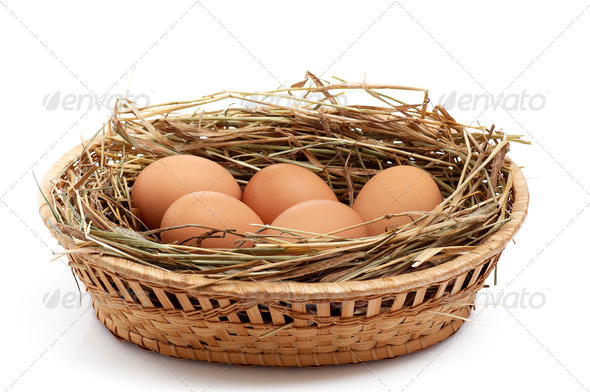 Chicken eggs and hay in  the brown basket . - Stock Photo - Images
