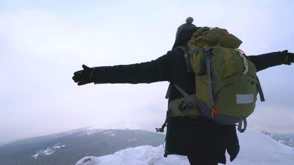 A Young Man, a Tourist, Stands on the Edge of a Snow-covered Mountain
