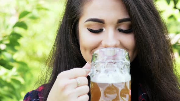 Portrait of Young Happy Beautiful Woman Which Drinks Beer From Glass, Quenches Thirst