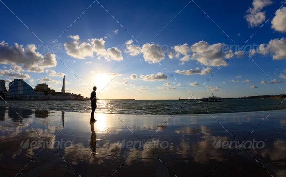 Silhouette of a boy on the seafront - Stock Photo - Images