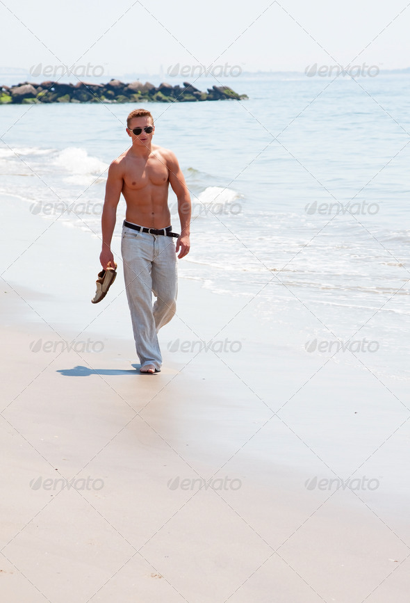 Handsome man walking on beach - Stock Photo - Images