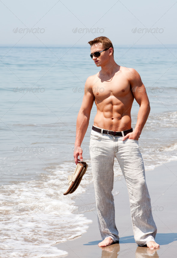 Handsome man standing on beach - Stock Photo - Images