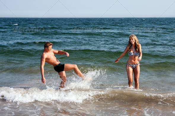 Couple playing in ocean water - Stock Photo - Images