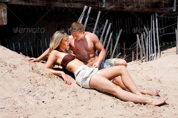 Couple laying in sand - Stock Photo - Images