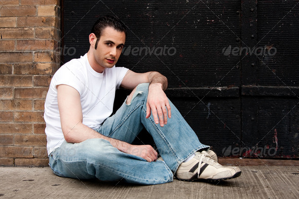 Man sitting on concrete - Stock Photo - Images