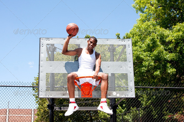 Champion basketball player sitting in hoop - Stock Photo - Images