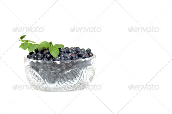 Bowl full whortleberries and green leaves on a white. - Stock Photo - Images