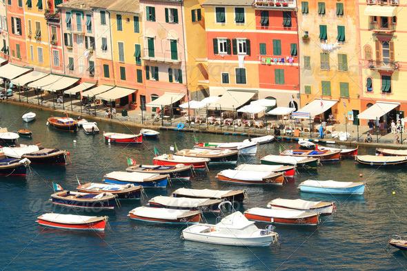 Boats floating along multicolored houses of Portofino. - Stock Photo - Images