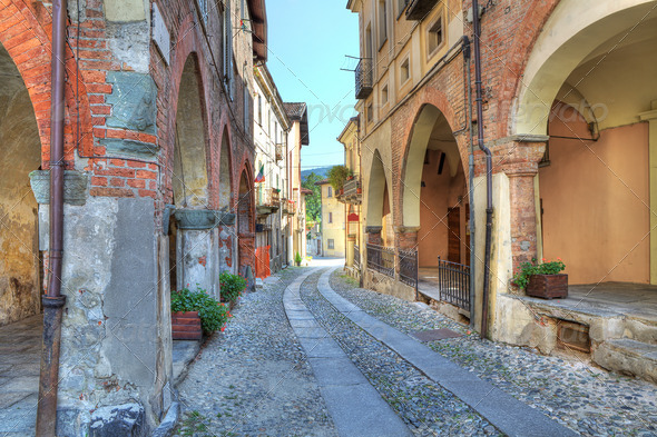 Old narrow street amont ancient houses in Avigliana, Italy. - Stock Photo - Images