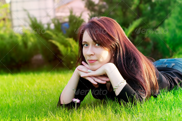 woman lying on green grass - Stock Photo - Images
