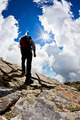 Rear view of a man hiking up a rock hill against a dramatic cloudy sky.  - PhotoDune Item for Sale